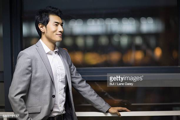 Young businessman standing by window
