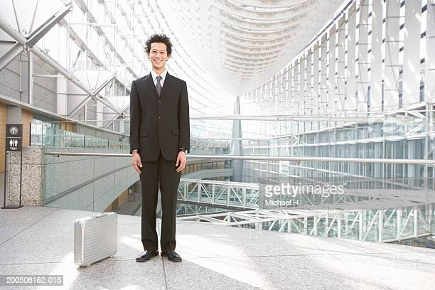 Young businessman standing in corridor, smiling, portrait