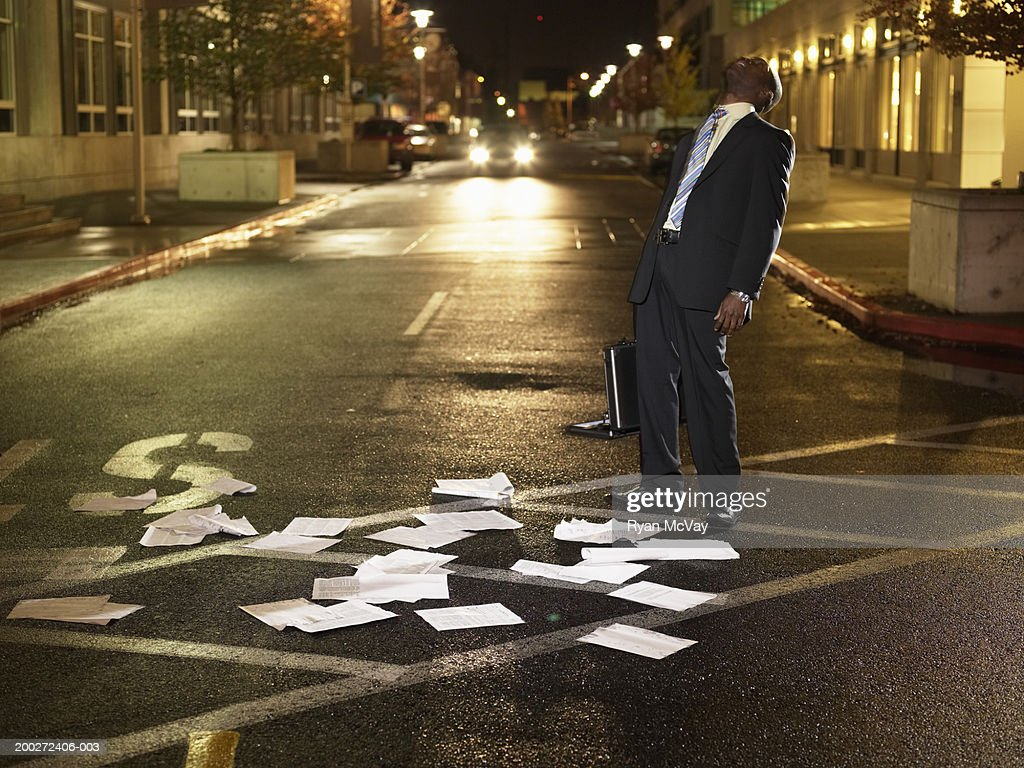 Young businessman standing in crosswalk, papers scattered on ground : Stock Photo