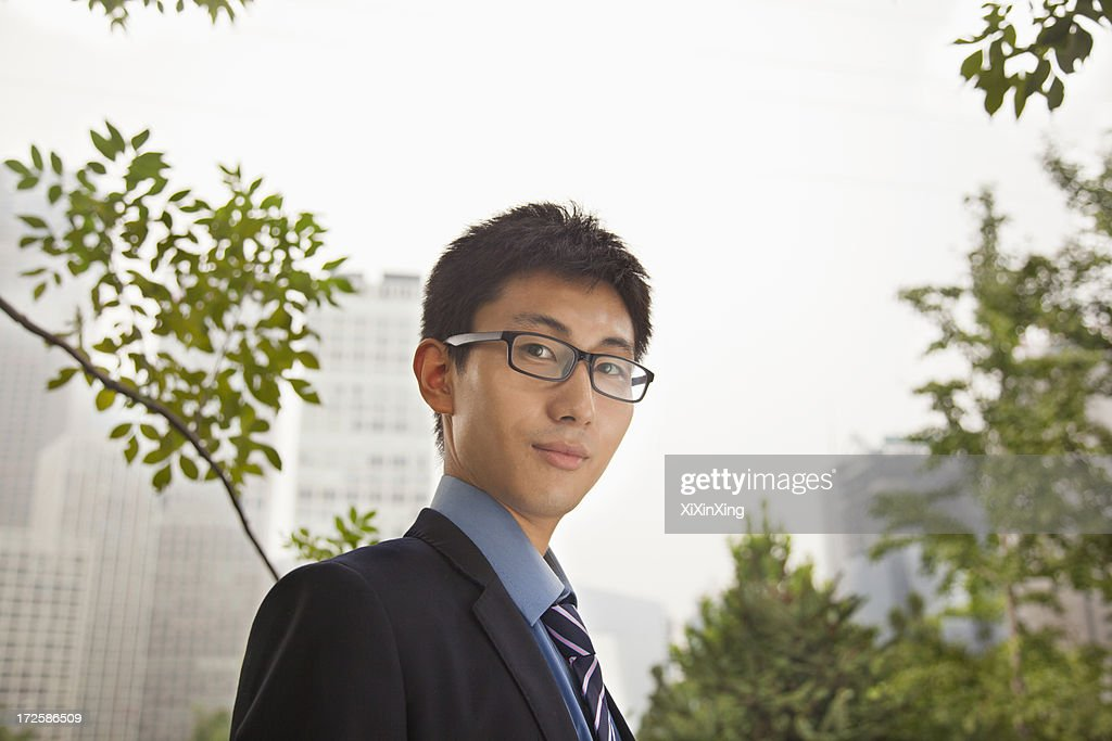Young businessman standing in the park, portrait : Stock Photo