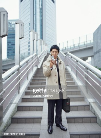 Young businessman standing on steps, holding mobile phone
