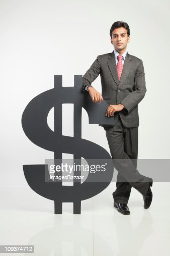 Young businessman standing with dollar sign, studio shot : Foto stock