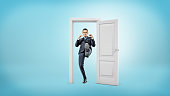 A young businessman stands in a small cut out doorframe and kicks a door open with his foot. Self-made executive. Fight bureaucracy. Get things done.