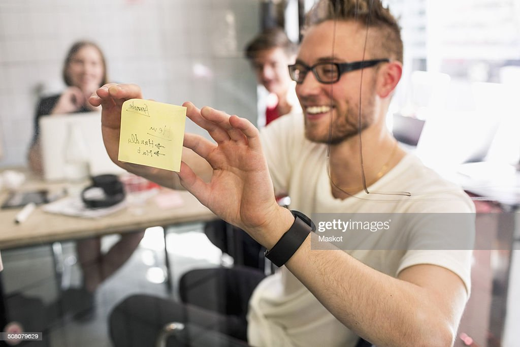 Young businessman sticking adhesive note on transparent glass with colleagues at background in new office