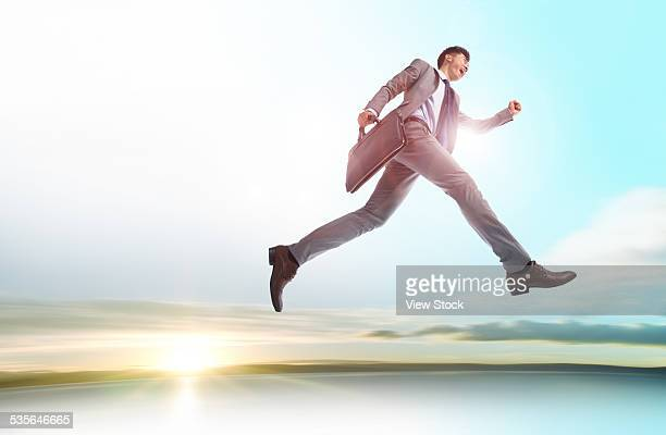 Young businessman striding in the air