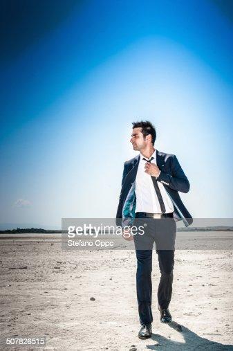 Young businessman striding through desert landscape alone