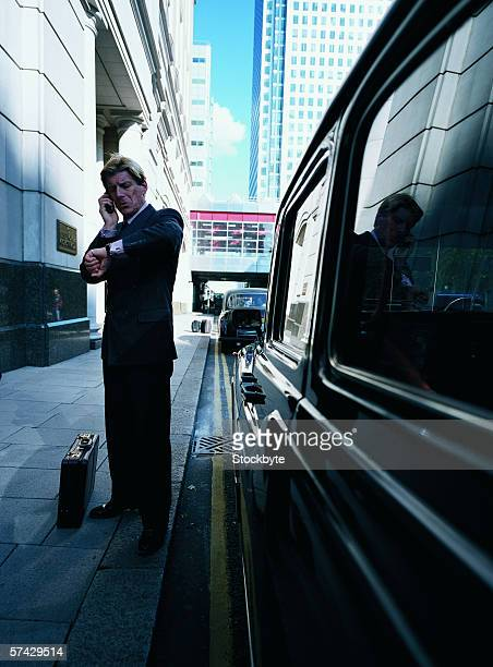 Young businessman talking on a mobile phone and looking at his wristwatch