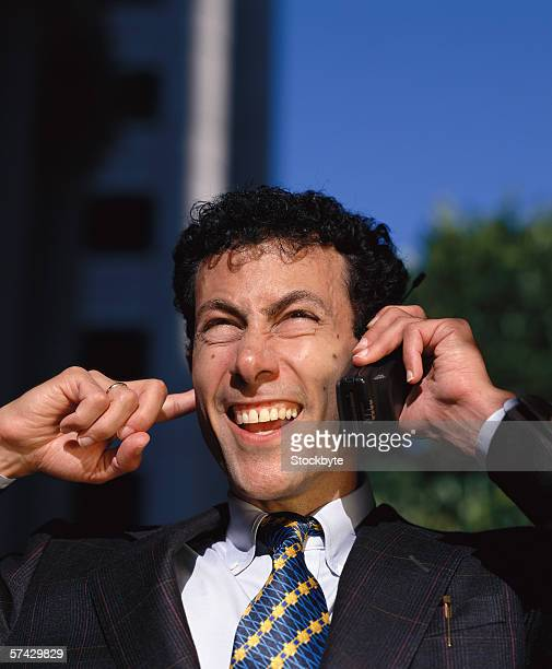 Young businessman talking on a mobile phone outdoors with his finger in his ear