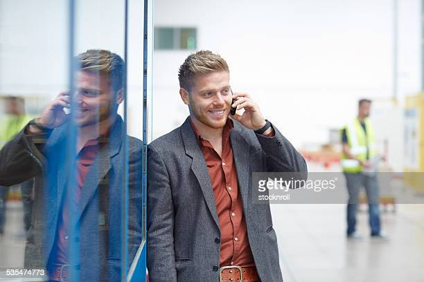 Young businessman talking on mobile phone while at factory shopfloor