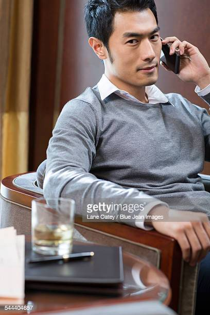Young businessman talking on phone in hotel room