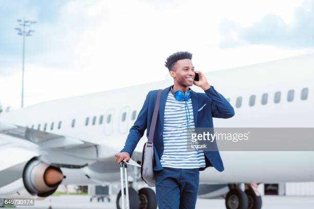 Young businessman talking on smart phone in front of airplane