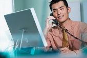 Young businessman talking on telephone