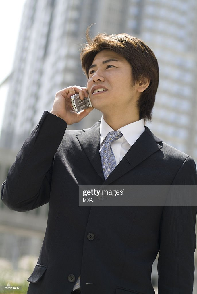 Young businessman talking over mobile phone : Stock Photo