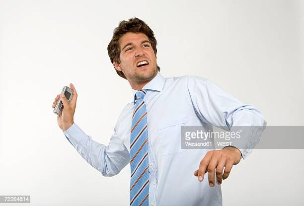 Young businessman throwing mobile phone, close-up
