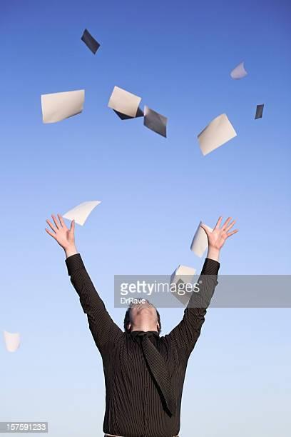 投げる若いビジネスマンの紙の空気、ブルースカイ