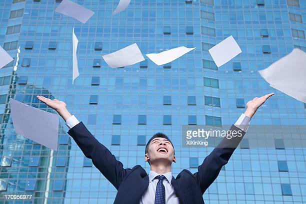 Young Businessman throwing paper with arms in the air