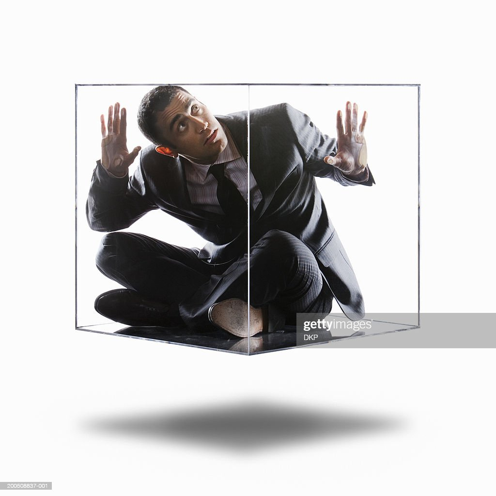 Young businessman trapped inside transparent box, looking up : Stock Photo