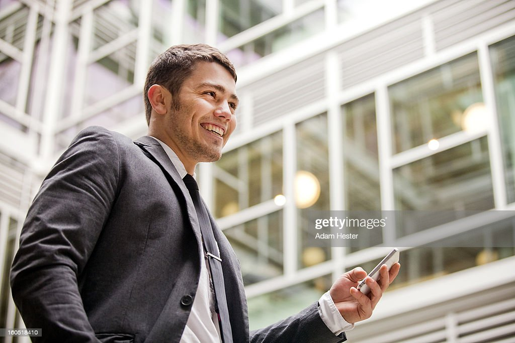 A young businessman using a cell phone downtown. : Stock Photo