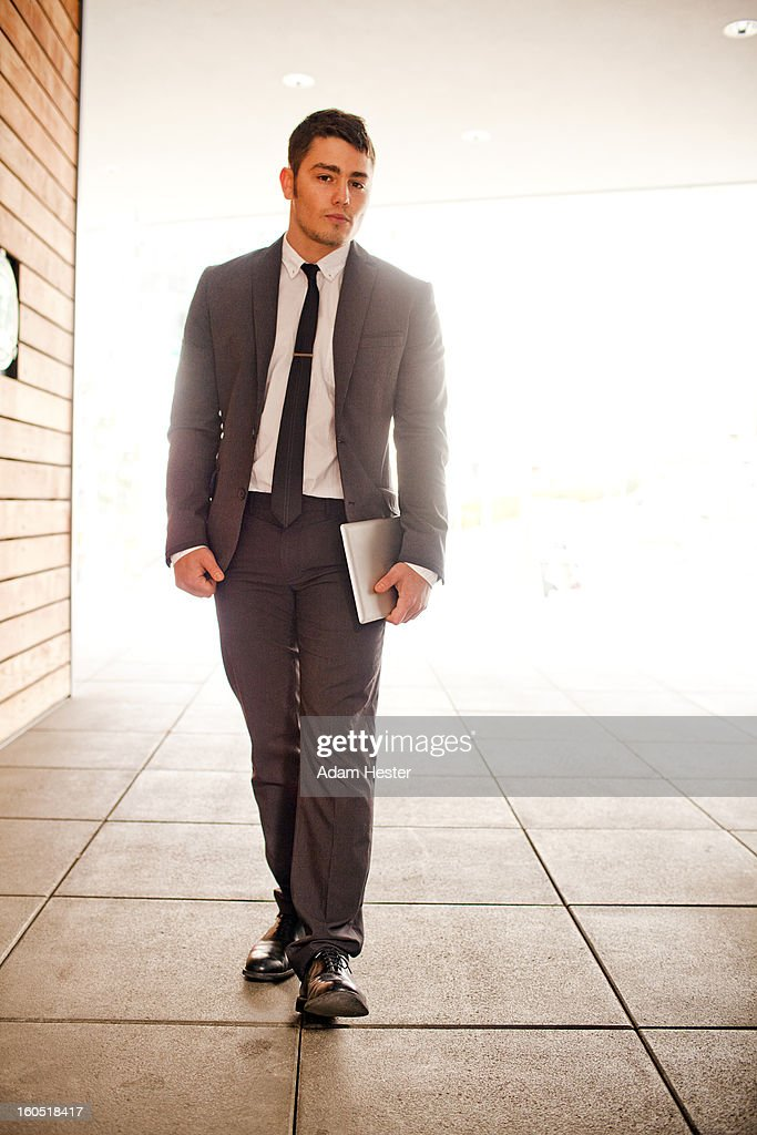 A young businessman using a tablet device downtown : Stock Photo