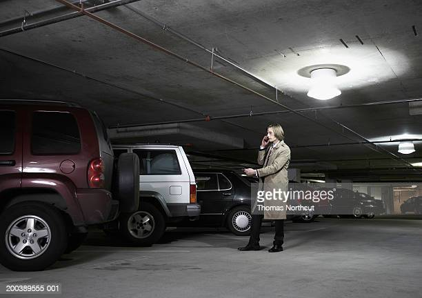 Young businessman using cell phone and car alarm remote control