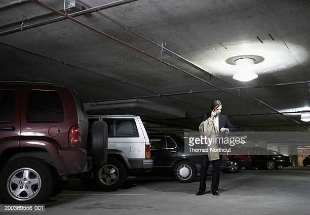 Young businessman using cell phone and checking time in parking garage