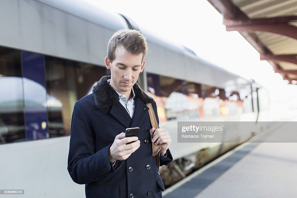 Young businessman using cell phone on railroad station
