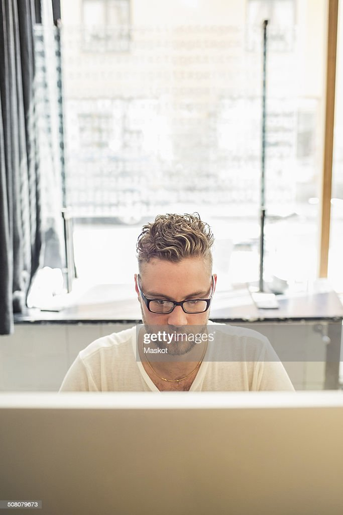 Young businessman using computer in creative office
