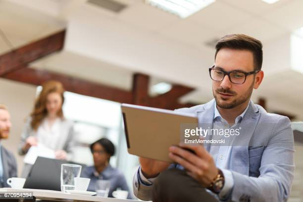 Young businessman using digital tablet and analyzing business report.