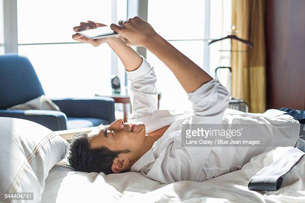 Young businessman using digital tablet in hotel room