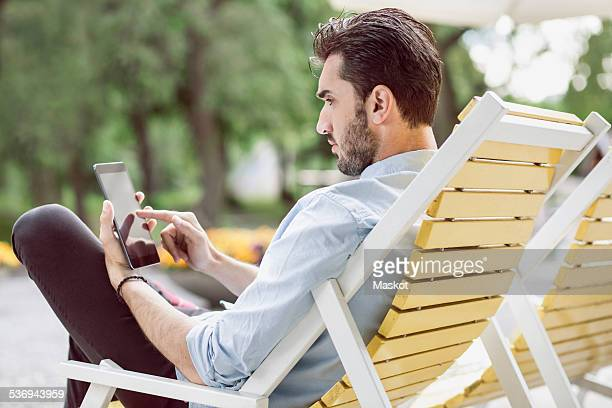 Young businessman using digital tablet on lounge chair at park