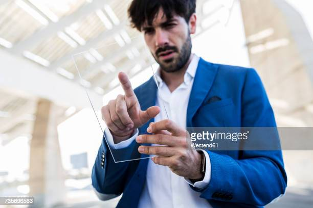 Young businessman using futuristic portable device