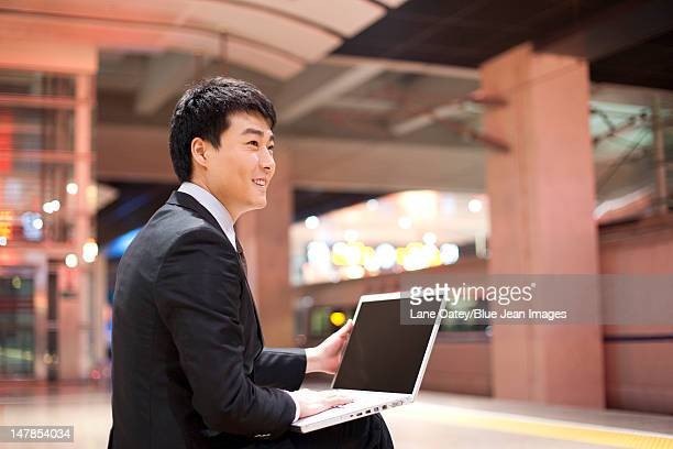Young businessman using his laptop at the train station