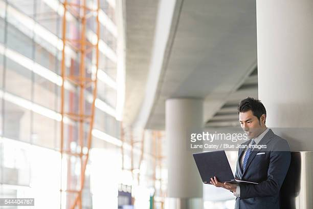 Young businessman using laptop in airport
