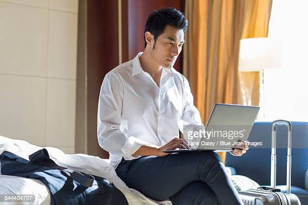 Young businessman using laptop in hotel room