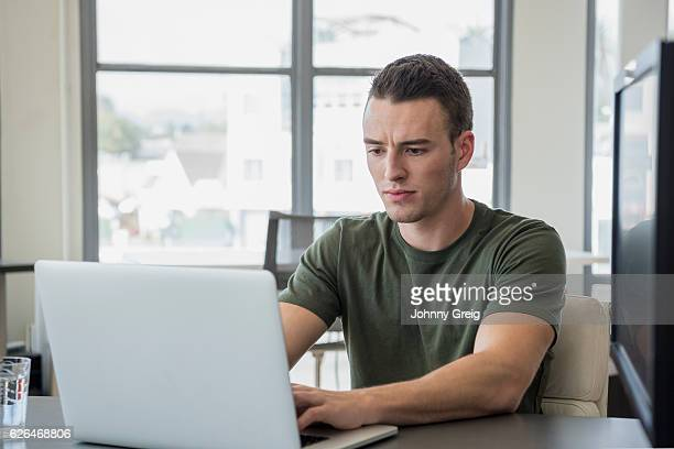 Young businessman using laptop with serious expression