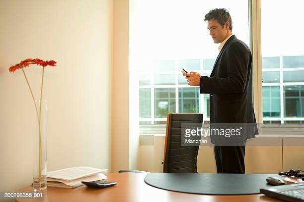 Young businessman using mobile phone in office