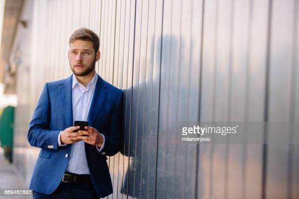Young businessman using mobile phone outdoors