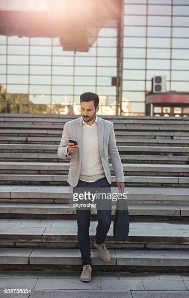 Young businessman using mobile phone while walking downstairs.