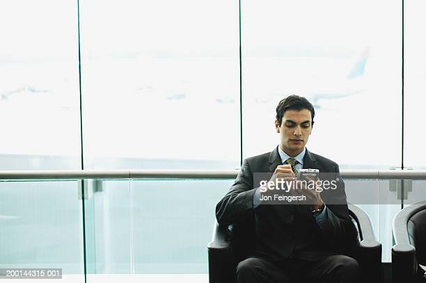 Young businessman using personal digital assistant in airport