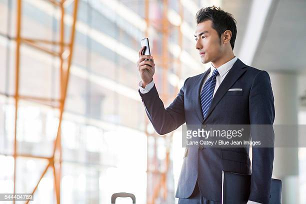 Young businessman using smart phone in airport