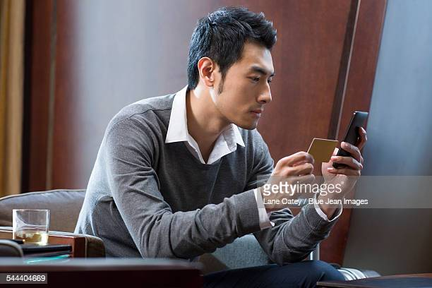 Young businessman using smart phone with a business card