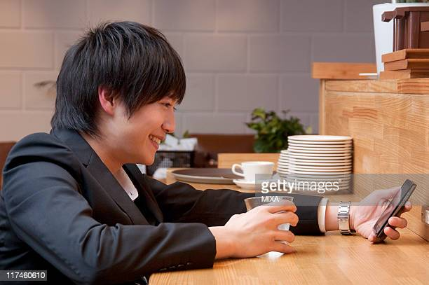 Young businessman using Smartphone at cafe