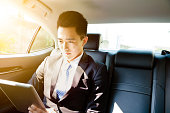 young businessman using tablet pc in car at morning