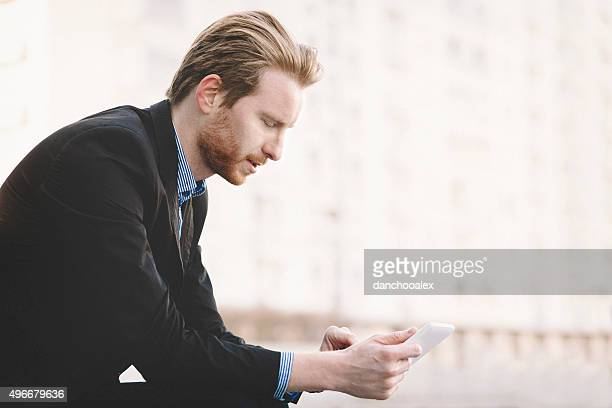 Young businessman using tablet pc in front of building