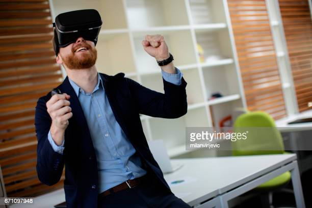Young businessman using virtual reality simulator headset in the office