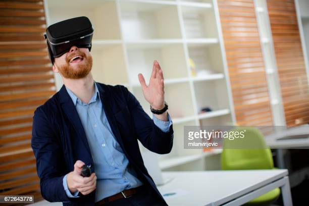 Young businessman using virtual reality simulator headset