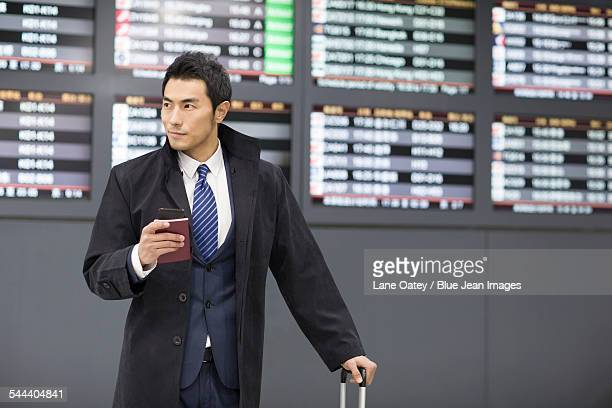 Young businessman waiting in airport with passport and smart phone