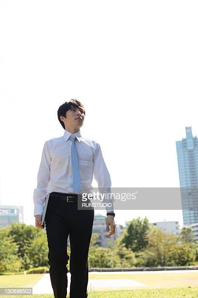 young businessman walking a Notebook PC