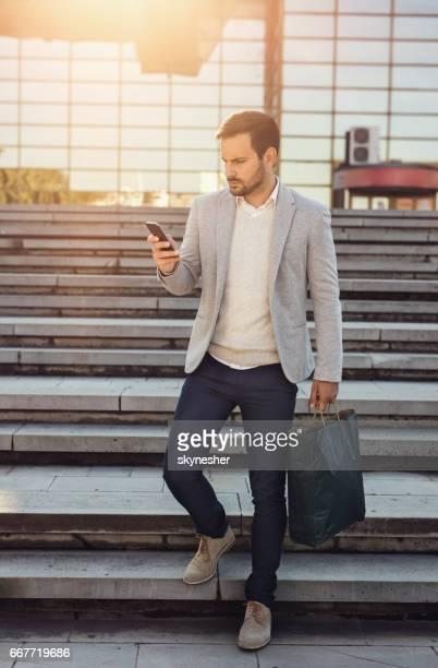 Jeune homme d'affaires de marche en bas tout en utilisant le téléphone intelligent.