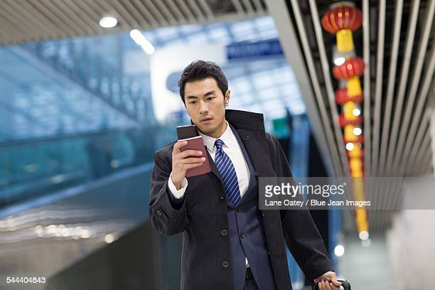 Young businessman walking in airport with passport and smart phone